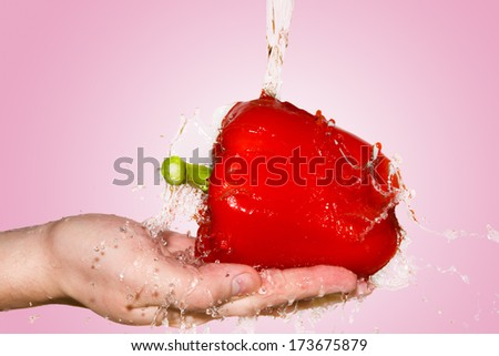 splash with red pepper lying in hand on pink background