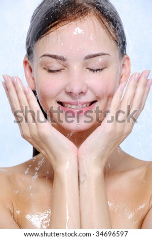 splashes and drops of water on the happy young  female face