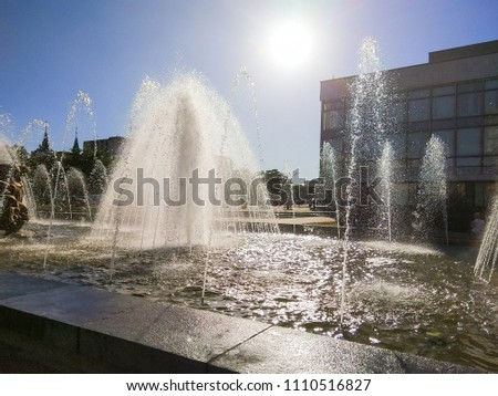 Splashes of a fountain in the city environment, city fountain on a sunny day, the sun's rays and water drops, preparation for the designer, a trip to Europe, art