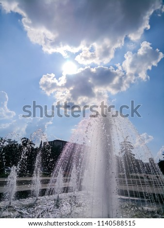 Splashes of fountain in the city environment, city fountain on a sunny day, the sun's rays and water drops, trip to Europe