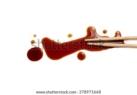 splashes of soy sauce and chopsticks isolated on white. wooden chopsticks dipped in soy sauce spilled. splashes and drops of isolated on white background. flat lay, top view