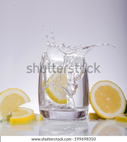 Splashes of water, lemon falling into a glass, isolated, reflection, white background