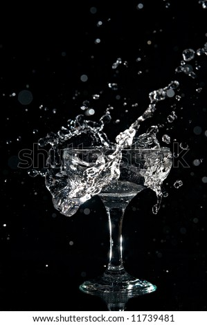 splashes water in goblet on black background