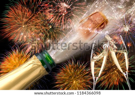 splashing bottle of champagne with flying cork and firework at Silvester 2019 #1184366098