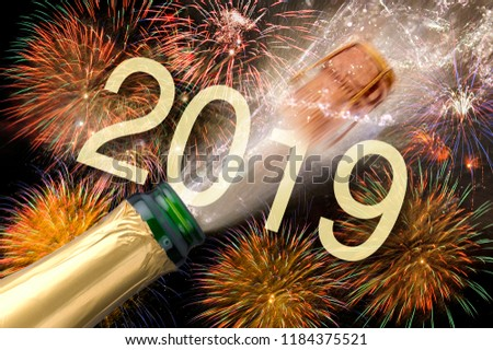 splashing bottle of champagne with flying cork and firework at Silvester 2019 #1184375521