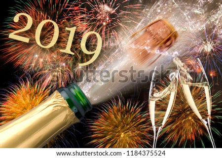 splashing bottle of champagne with flying cork and firework at Silvester 2019 #1184375524