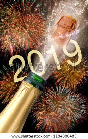 splashing bottle of champagne with flying cork and firework at Silvester 2019 #1184380483