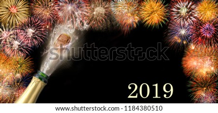 splashing bottle of champagne with flying cork and firework at Silvester 2019 #1184380510