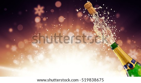 Splashing bottle of champagne with flying cork over fireworks background. Celebration concept, free space for text #519838675
