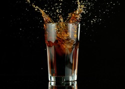 Splashing cola drink from glass, isolated on black background. Fresh summer drink, freeze motion.