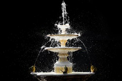 Splashing fountain in four levels on dark background