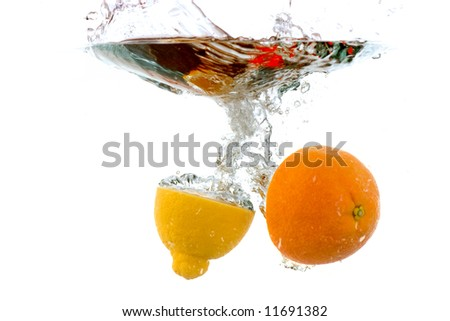 splashing fruit - lemon and orange halves splashing into water, against white