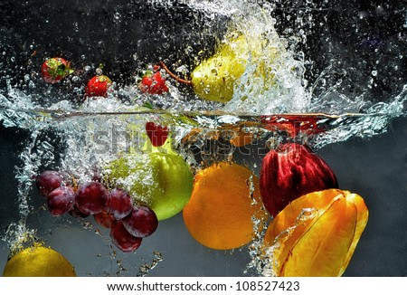 Splashing fruit on water. Fresh Fruit and Vegetables being  shot as they submerged under water.  Illustration of Washing food before being process further into a healthy and natural food - stock photo