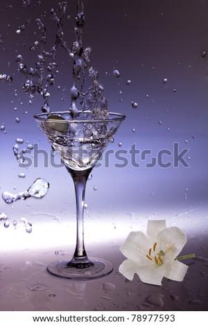 Splashing olive into a martini glass - stock photo