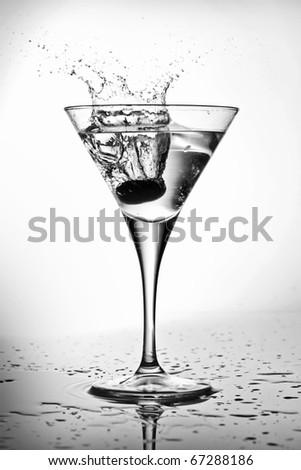 Splashing olive into a martini glass (black and white)