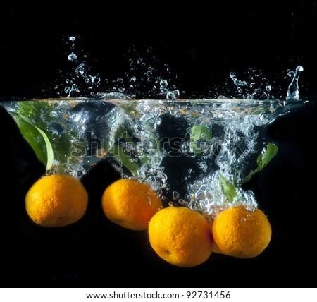 Splashing orange fruit into water on black