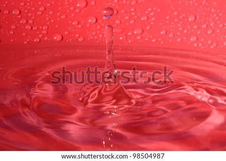 splashing water droplets on red background