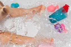 Splashing water in the bathtub with children's toys while bathing.