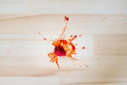 Splatted scattered strawberry on the wooden floor, concept of dirty floor in home.