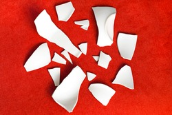 Splinters and Fragments of the broken white ware. Metaphor of a family quarrel. Broken Plate, glass. The concept of accidents in the kitchen. Pieces of shattered dishes.
