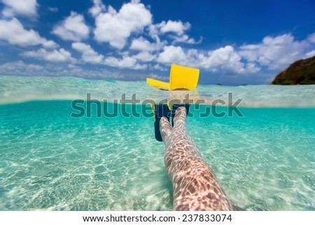 Split above and underwater photo of woman legs with fins at shallow water on tropical beach