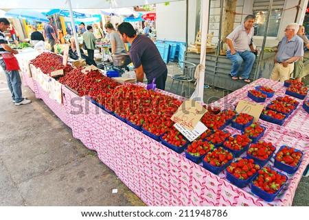 SPLIT, CROATIA, MAY 26, 2011. People selling red strawberried in the main open air market in Split, Croatia, on May 26th, 2011.
