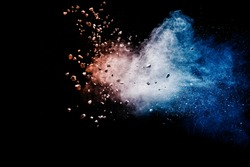 Split debris of stone exploding with blue red powder against black background.