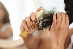 Split Ends Remedy. Unrecognizable Black Woman Applying Moisturising Spray To Her Curly Hair At Home, Closeup