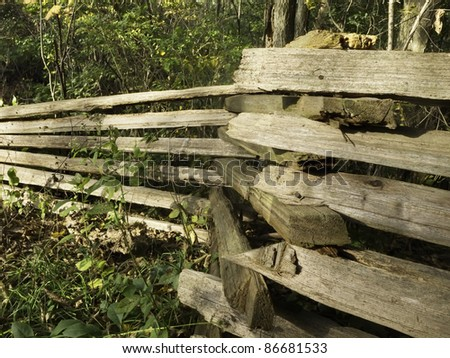 Split rail fence in woods - stock photo