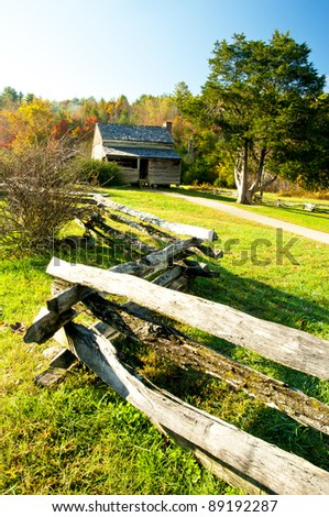Split-rail fence leading to an old home in fall
