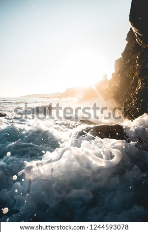 Split Second Blue Wave Splash Crashing Against Rock Cliff with Colorful Blue Sky  and Sunshine in Scenic Background in Tranquil Tropical Island Paradise Nature Scene of Maui Hawaii #1244593078