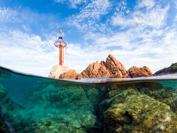 Split-shot, over-under shot. Stunning view of half underwater half sky with rocks ad a red navigational mark. Liscia Ruja, Costa Smeralda, Sardinia, Italy.