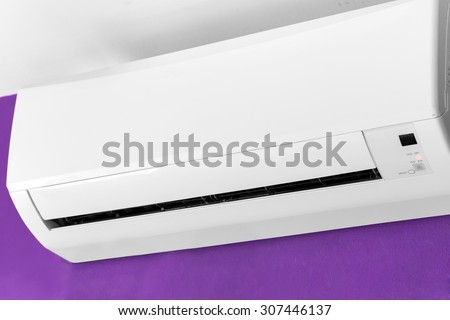 Split-system air conditioner on violet wall
