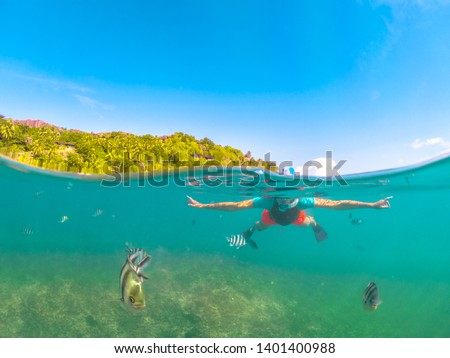 Split view of female apnea under and above the sea. Snorkeling dress woman at Felicite, La Digue satellite island, Seychelles. Travel lifestyle watersport activity. Fish and sealife in foreground. #1401400988