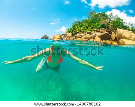 Split view of snorkel woman underwater St. Pierre Island, Seychelles. Female apnea sealife under and above Indian Ocean. Tropical destination holiday concept. Travel lifestyle watersport activity. #1400780102