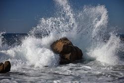 splits waves against rocks in the sea