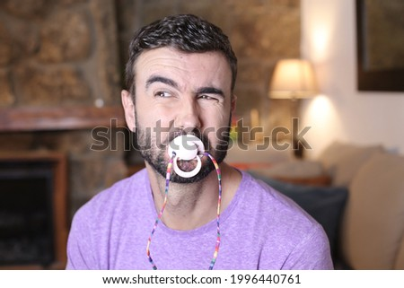 Spoiled grown up man licking a pacifier to control a tantrum Stok fotoğraf ©