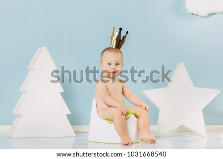 spoiled kid concept - funny preschool child with golden crown on head.Little boy sitting on the pot.Kid boy sitting on chamber pot. #1031668540