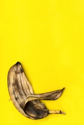 spoiled rotten banana, peel isolated on yellow background with copy space.