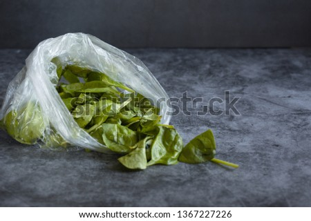 Spoiled  spinach is in a plastic bag on a dark background. Concept. Polluting to store vegetables in these packets. Copy space. #1367227226