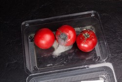 Spoiled tomatoes with mold in disposable plastic container. Organic food waste in supermarkets. Incorrect long-term storage. Dark textured stone background.