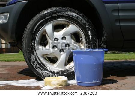 Sponge and bucket by car wheel