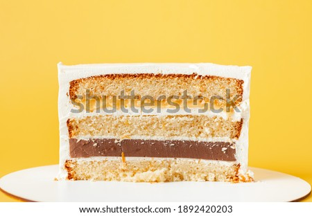 Sponge cake cut. Layered cake with soft caramel, lemon curt and cream cheese frosting on the yellow background Imagine de stoc ©