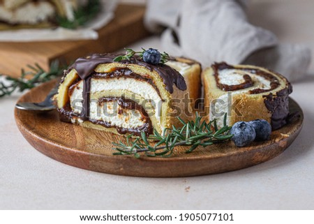 Sponge cake roll with chocolate and cream cheese decorated with chocolate glaze, blueberry and rosemary on parchment, light concrete background. Biscuit swiss roll. Photo stock ©