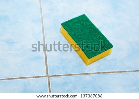 sponge cleaning the bathroom tiles