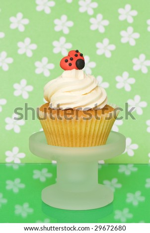 Sponge cupcake with butter cream icing and ladybug decoration