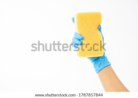 Sponge for washing and cleaning in female hand. Hand in a latex glove isolated on white. A hand in a glove holds a sponge for washing and cleaning. Foto stock ©