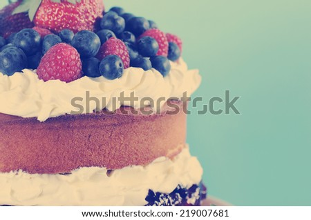 Sponge Layer Cake with fresh whipped cream, raspberry jelly and raspberries, strawberries and blueberries with retro vintage style filter.