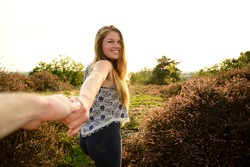 Spontaneous and loving girlfriend taking her boyfriend by the hand and guiding him lovingly while walking through nature on a beautiful summer day. Loving couple.