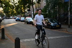 Spontaneous and smiling Dutch male student riding on his bicycle through an old and cosy street in Amsterdam, the Netherlands.